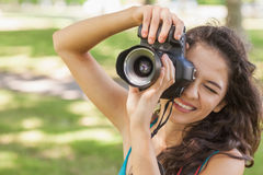 Cute brunette woman taking a picture with her camera Stock Images