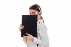 Cute brunette woman working in call center with headphones and microphone hide her smile behind a blackboard isolated on Royalty Free Stock Photo