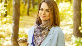 Cute young woman with cup of coffee in the autumn park stock video