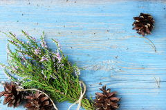 Cute bunch of natural wooden erica with a few piny cones on wooden background. Traditional rustic decor elements. Royalty Free Stock Photography