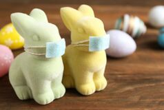 Free Cute Bunny Figures In Protective Masks Near Dyed Eggs On Wooden Table. Easter Holiday During COVID-19 Quarantine Royalty Free Stock Photo - 213329275