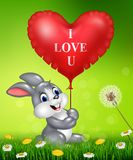 Cute bunny holding red heart balloons on green grass Stock Photography