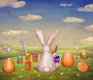 A cute bunny painting of egg for easter  on a hill surrounded by easter eggs Royalty Free Stock Photos