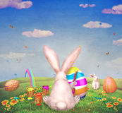 A cute bunny painting of egg for easter  on a hill surrounded by easter eggs Stock Photography