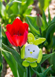 Cute bunny toy hidding among red tulips. Royalty Free Stock Photos