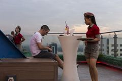 Cute Burmese waitress in shorts waiting for tourist to pay for his drink in open-air terrace bar stock photography