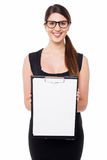 Cute business executive showing blank clipboard Stock Image