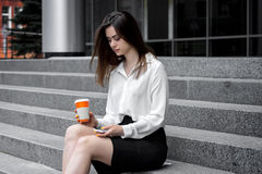 Cute business girl sitting on the stairs keeps coffee and stares at the phone Royalty Free Stock Photography