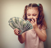 Cute business kid girl holding money and counting the revenue. Royalty Free Stock Photography