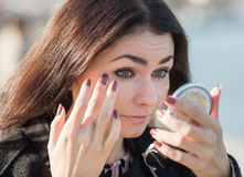 Cute business woman adjusting her make-up Stock Image