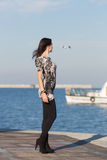 Cute business woman observes white boat in sea Royalty Free Stock Photos