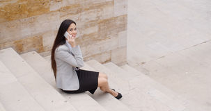 Cute business woman sitting on steps with phone Royalty Free Stock Image