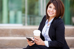 Cute businesswoman with cell phone. Happy Hispanic business woman sending a text message on her cell phone and drinking some coffee Royalty Free Stock Photo
