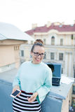 Cute businesswoman in eyeglasses talking on the phone standing on the roof of the house in the old town. Next to it are a laptop, royalty free stock images