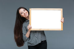 Cute businesswoman holding blank board. Happy cute businesswoman holding blank board over gray background Royalty Free Stock Photography