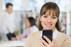 Cute businesswoman on mobile phone in office, sms, Royalty Free Stock Photography