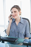 Cute businesswoman phoning with her smartphone sitting at her desk Royalty Free Stock Photography