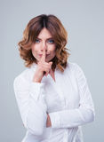 Cute businesswoman showing finger over lips Stock Photography