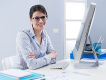 Cute businesswoman smiling at desk Stock Photo