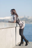 Cute businesswoman  stands by the concrete wall Royalty Free Stock Image