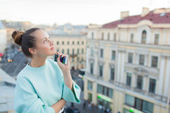 Cute businesswoman is thinking and smiling on the roof in the old town.  Royalty Free Stock Photography
