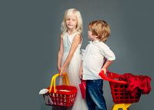 Cute buyer customer client hold shopping cart. Girl and boy children shopping. Couple kids hold plastic shopping basket. Toy. Kids store. Mall shopping. Buy stock photography