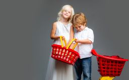 Cute buyer customer client hold shopping cart. Girl and boy children shopping. Kids store. Couple kids hold plastic. Shopping basket toy. Buy with discount royalty free stock photography