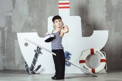 Cabin boy playing with paddle in front of stylized ship. Cute cabin boy in striped t-shirt and sailor cap playing with paddle in front of stylized ship, studio royalty free stock image