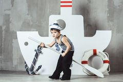 Cabin boy playing with paddle in front of stylized ship. Cute cabin boy in striped t-shirt and sailor cap playing with paddle in front of stylized ship, studio stock photo