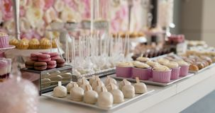 Cute candy bar with various cakes and candies. Wedding candybar. stock video footage