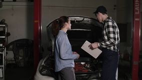 Cute car or automotive technician wearing work robe and a cap is meeting with his female clients and hears out. Complaints about her vehicle stock video