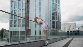 Cute carefree millenial hipster girl having fun and smile, urban city streets at background. Slow motion stock video