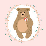 Cute cartoon bear with a lollipop in his paws and floral wreath. Stock Image