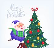 Cute cartoon blue suit Santa Claus decorating Christmas tree Merry Christmas vector illustration Greeting card poster. Stock Images