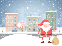 Cute cartoon Santa Claus  with bag in the small town on holidays. Stock Photos