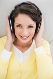 Cute casual brunette in yellow cardigan enjoying music Royalty Free Stock Images