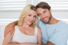 Cute casual couple sitting on couch smiling at camera Royalty Free Stock Image