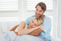 Cute casual couple sitting on couch under blanket stock photos