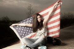 Cute casual girl holding stars and stripes behind Stock Images