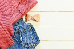 Womens casual clothes. Female blue jeans, knit pink sweater, hair grip on a wooden background with empty space for text. Top view. Cute casual outfit. Casual royalty free stock images