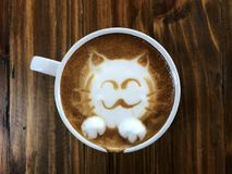 Cute cat face latte art coffee in white cup. On wooden table ; love coffee, Cute Neko latte art coffee Stock Photos