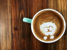 Cute cat face latte art coffee in white cup. On wooden table ; love coffee, Cute Neko latte art coffee Royalty Free Stock Photos