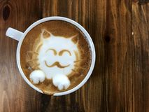 Cute cat face latte art coffee in white cup stock photography
