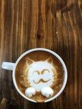 Cute cat face latte art coffee in white cup. On wooden table ; love coffee, Cute Neko latte art coffee Stock Image
