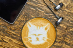 Cute cat latte art. Coffee glass and earphones. Songs to start the day stock photography