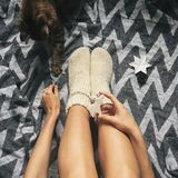 Cute cat playing with holiday ornaments at girl legs in christmas woolen socks and stylish reindeer toy in hands. Top view. Atmospheric cozy image, warm winter stock photography