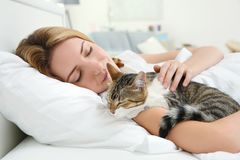 Cute cat and young woman relaxing. On bed Stock Photo