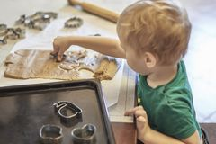 Cute caucasian baby boy helps in kitchen, making coockies. Casual lifestyle in home interior, pretty child alone. royalty free stock photography