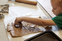 Cute caucasian baby boy helps in kitchen, making homemade coockies. Casual lifestyle in home interior, pretty child, holiday conce. Pt, rolling pin, coockie stock photography