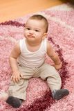 Cute caucasian baby sitting on the carpet Stock Image